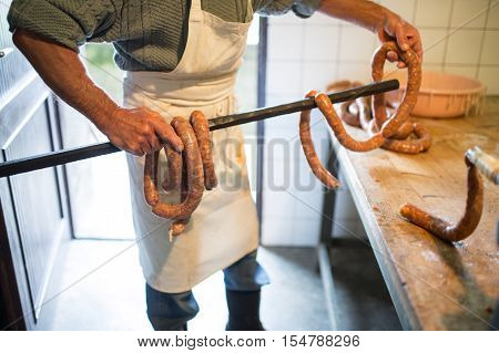 Unrecognizable man hanging homemade raw sausages on wooden stick, making them the traditional way. Close up.