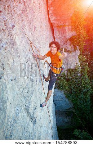 male rock climber. rock climber climbs on a rocky wall. man show ThumbUp gesture, sign.