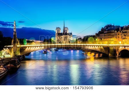 Notre dame de Paris at night and the seine river France in the city of Paris in France