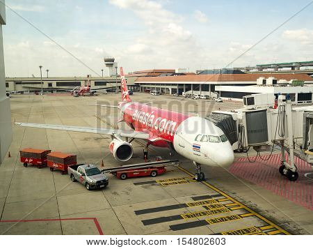 BANGKOK THAILAND-OCT 21 2016: Airplane Air Asia Airways parking on Bangkok International Airport (Don Muang) Bangkok. Engineers are maintain the engine of the aircraftThailand. Oct 21 2016.