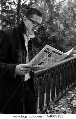 modern man reading a newspaper and smoking