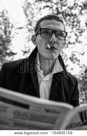 imposing man reading a newspaper and smoking