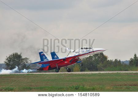 Kiev Region Ukraine - October 2 2010: Sukhoi Su-30LL fighter plane in Russian flag colors is landing with smoke on the runway