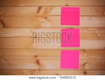 Three pink sticky notes on wooden background
