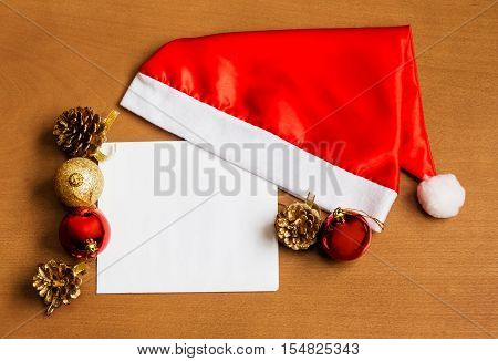 Christmas card with Santa hat and christmas decorations on wooden background