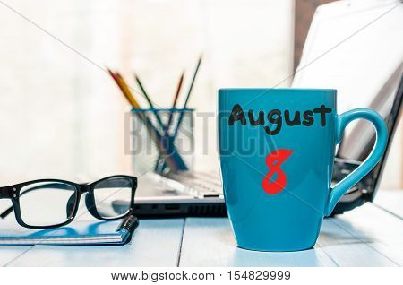 August 8th. Day 8 of month, morning coffee cup with calendar on freelance workplace background. Summer time. Empty space for text.