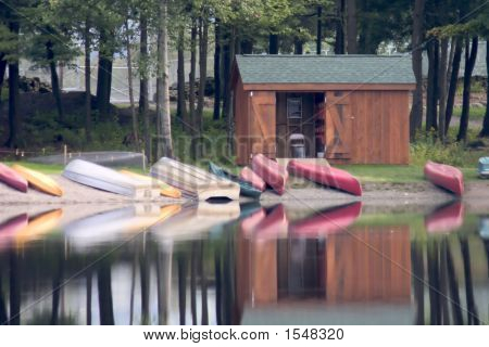Rustic Boat House With Canoes Reflecting In Lake