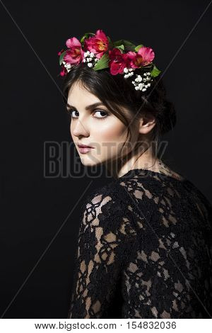Beautiful black-haired brunette woman with a rim of fresh red and white flowers and green petals on her head in a black lace dress on black background.