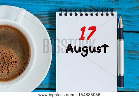 August 17th. Day 17 of month, loose-leaf calendar on blue background with morning coffee cup. Summer time. Top view.