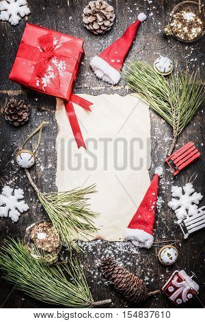 various Christmas decorations around blank sheet of paper gift box Santa hat and snowflakes on rustic wooden background top view frame vertical