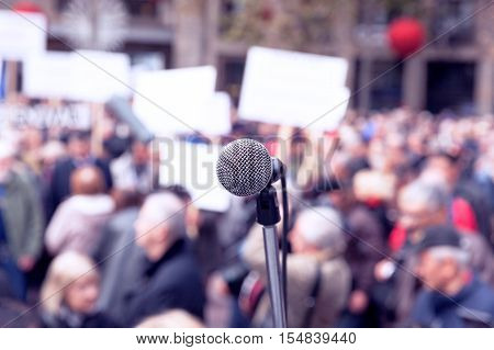 Microphone in focus against blurred protesters. Protest. Demonstration.