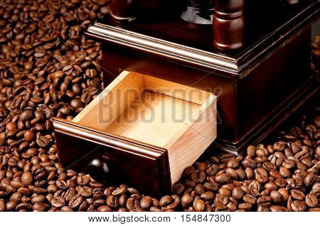 Close-up of manual retro coffee grinder with coffee beans - top view. Coffee mill on many roasted coffee beans.