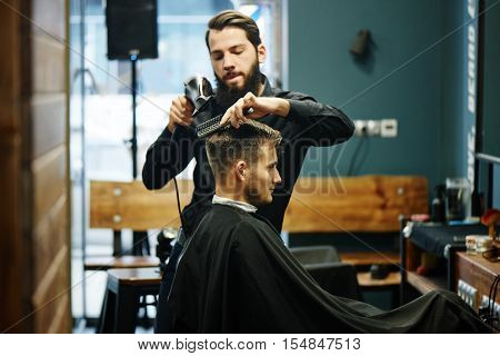 The Barber man in the process of drying a client's hair with a Hairdryer at the hairdresser