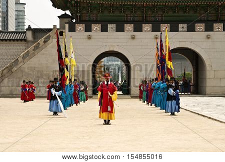 SEOUL KOREA - MAY 17 2015: Armed guards in traditional costume guard the gate at Gyeongbokgung Palace a tourist landmark in Seoul South Korea