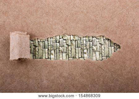 Brown color torn notepaper on a brick wall background