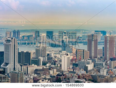 Tokyo Japan - September 26 2016: Aerial view since shot off Observatory tower. Rainbow bridge ocean inlets multitude of highrises and buildings under bluish sky hazy in the far distance. NEC buildiing.