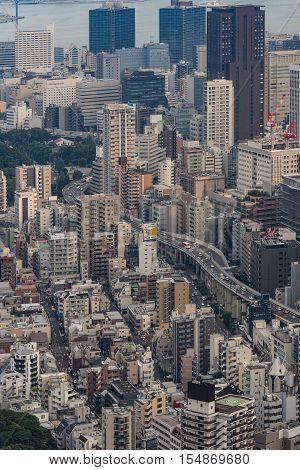 Tokyo Japan - September 26 2016: Aerial view since shot off Observatory tower. Multi-level highway meanders between highrise buildings in Tokyo. Part of port water in shot.