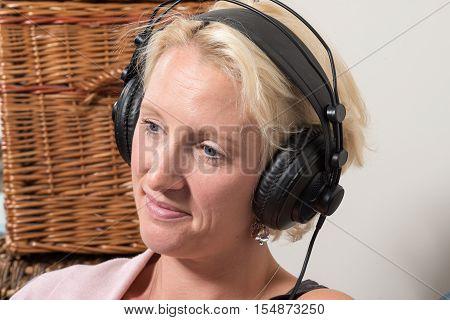 Sitting Blonde Woman Wearing Headphones Tilts Head And Smiles