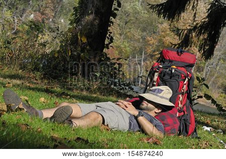 A young male hiker taking a nap on the grass by campsite