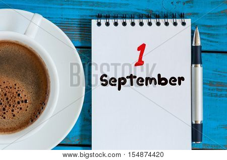 September 1st. Day 1 of month, loose-leaf calendar on blue background with morning coffee cup. Autumn time. Empty space for text. Back to school.