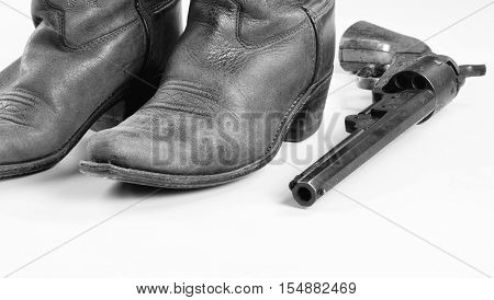 Old cowboy boots and cowboy pistol in black and white with room for your type..