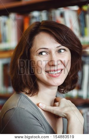 Closeup portrait of smiling middle age mature woman student in library looking away teacher librarian profession back to school concept