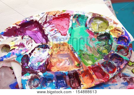 Beautiful colorful textured background paint strokes on paper and left overs residues of paints in palette colour array on table spots and blotches stains