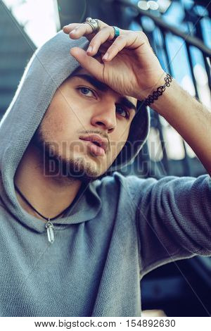 Conceptual art portrait of beautiful handsome gothic young middle east brunette man with blue eyes beard wearing blue hoodie outside in street looking in camera touching his head