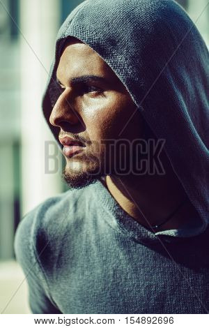 Closeup conceptual art portrait of beautiful handsome gothic young middle east brunette man with beard wearing blue gery hoodie outside in street looking away profile