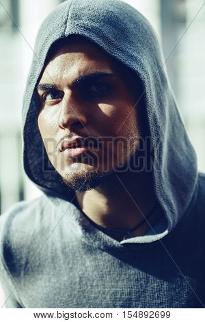 Closeup conceptual art portrait of beautiful handsome gothic young middle east brunette man with beard wearing blue gery hoodie outside in street looking in camera
