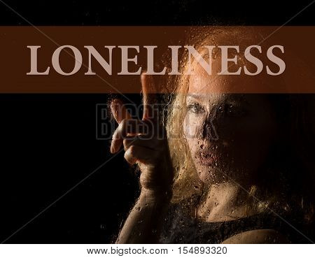 loneliness written on virtual screen. hand of young woman melancholy and sad at the window in the rain