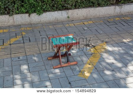 Small wooden folding stool stay alone on a pavement. Colorful stool in centre of frame.
