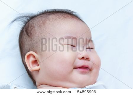 Healthy children. Closeup cute asian baby sleep sweet dreams. A three months adorable sleeping baby girl on white background.