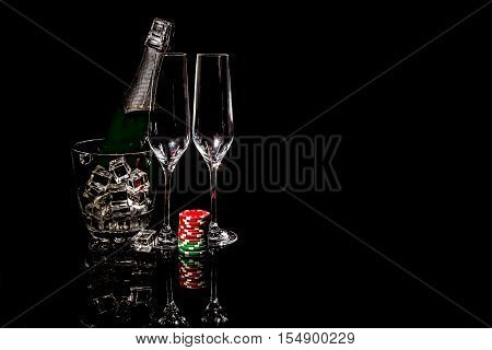Bottle of champagne in an ice bucket with two wineglasses and colorful chips
