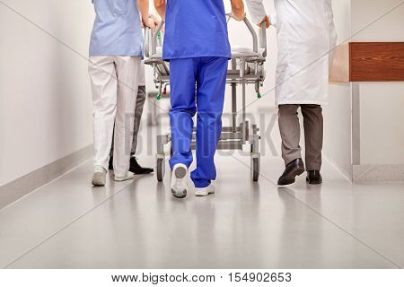 profession, people, healthcare, reanimation and medicine concept - group of medics or doctors carrying hospital gurney to emergency room