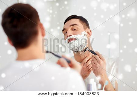 beauty, hygiene, shaving, grooming and people concept - young man looking to mirror and shaving beard with manual razor blade at home bathroom over snow
