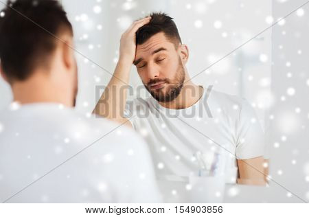 morning, awakening, hangover and people concept - sleepy young man in front of mirror at bathroom over snow
