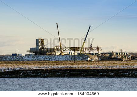 Works for the installation of the oil rig in the oilfield. River foreground. Derrick and cranes background. Oil and gas concept.