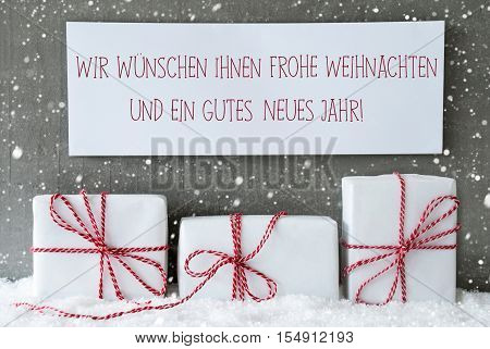 Label With German Text Frohe Weihnachten Und Ein Gutes Neues Jahr Means Merry Christmas And Happy New Year. Three Christmas Gifts Or Presents On Snow. Cement Wall As Background With Snowflakes.