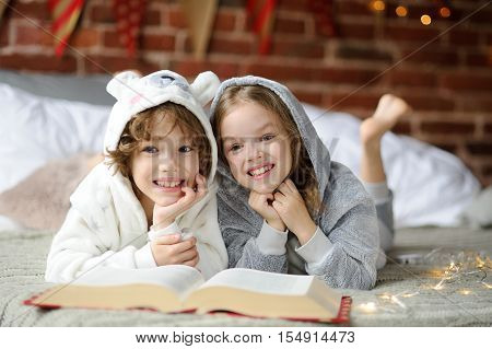 Christmas Holidays. Two children lay on a bed in soft pyjamas. Bedroom is decorated by christmas garlands. The children have a great book with Christmas tales. Christmas - magic time. Merry Christmas.