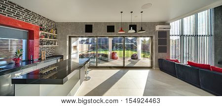 Interior in a modern style with a kitchen zone with a bar, concrete and brick walls, large windows and a door. On the right there is dark sofa with red pillows. Outside there is a terrace and a lawn.