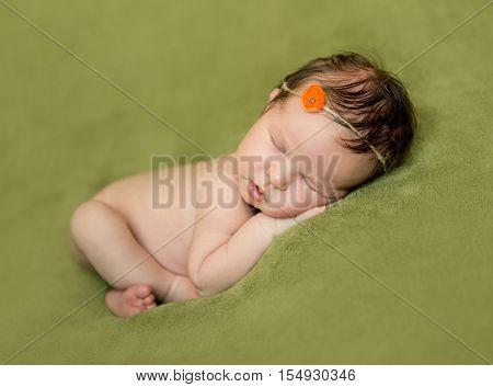 bare newborn baby with headband lying on a green blanket