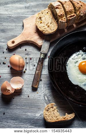Freshly fried egg and eggshell on old wooden table