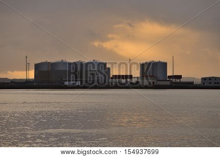 industrial repositories for oil and gas in the harbor at sunset