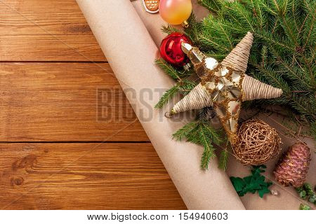 Prepare for christmas tree decoration background with copy space on wood. Winter Holiday eve. Xmas decor, fir tree and garlands concept. Ornaments, present packaging paper, stars and balls