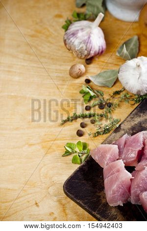 Layout of raw ingredients for fricassee including meat herbs and spices with place for text