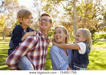 Parents carrying two young kids in park turn to look at son