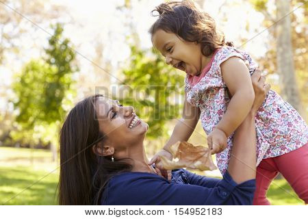 Asian mixed race mum and young daughter playing in park