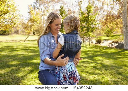 Mother and daughter embracing in park, three quarter length