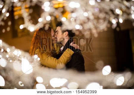 Couple kissing in street with christmas lights in foreground
